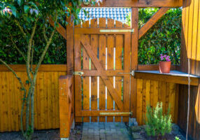 Wooden gate and fence on the back of the home garden. The gate is closed with a padlock.